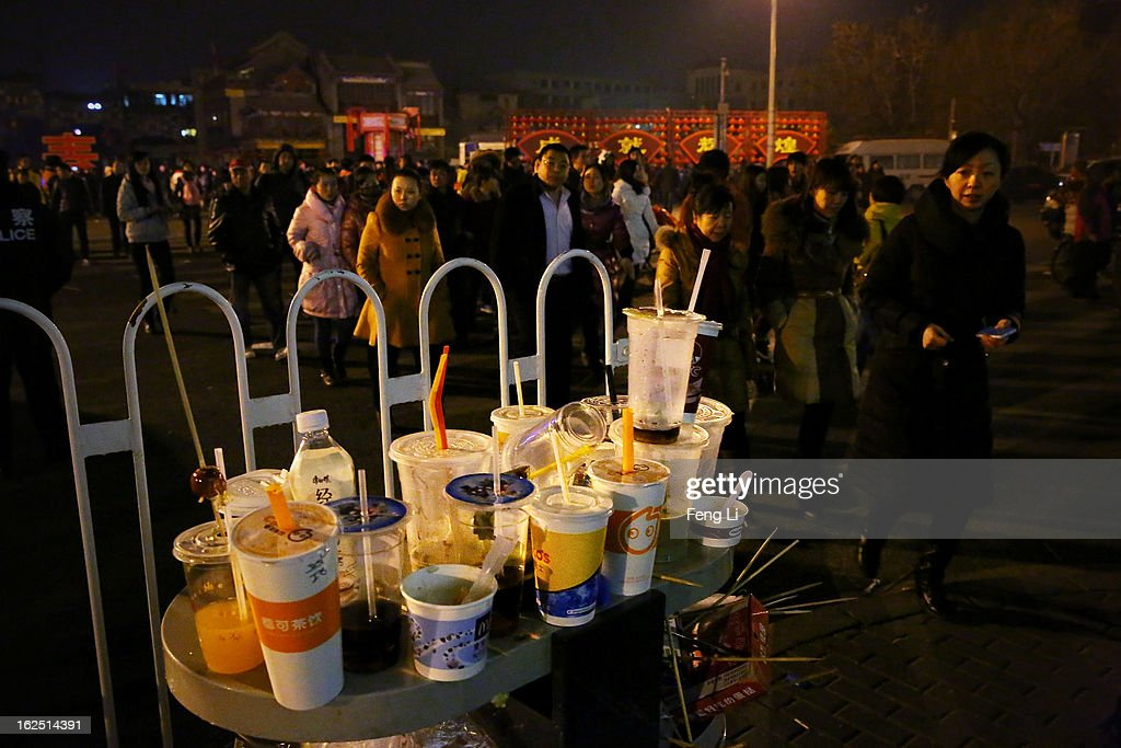 Chinese people walk past a full trash after visiting the ancient shopping area Qianmen Avenue during the Lantern Festival which falls on February 24 and traditionally marks the end of the Lunar New Year celebrations on February 24, 2013 in Beijing, China. The Lantern Festival is a Chinese festival celebrated on the fifteenth day of the first month in the lunar new year in the Chinese calendar.