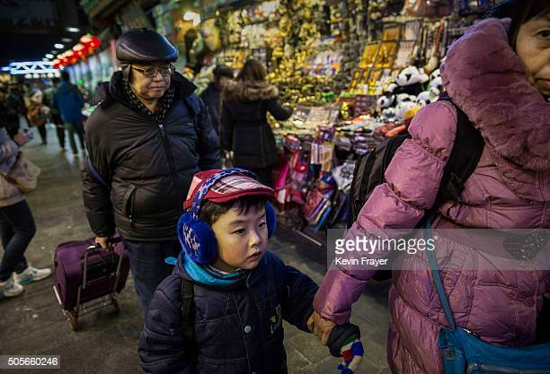 Chinese people walk through a market on January 19 2016 in Beijing China In 2015 China's economy grew at its slowest rate in a quarter century data...