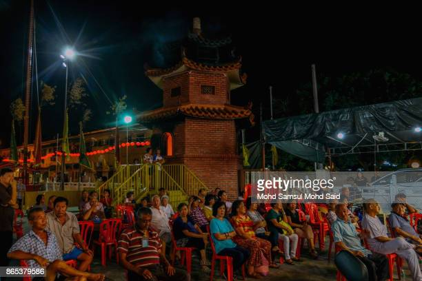 Chinese people watch a singing show as a part of entertainment during The Nine Emperor Gods Festival inside the temple on October 23 2017 in Klang...