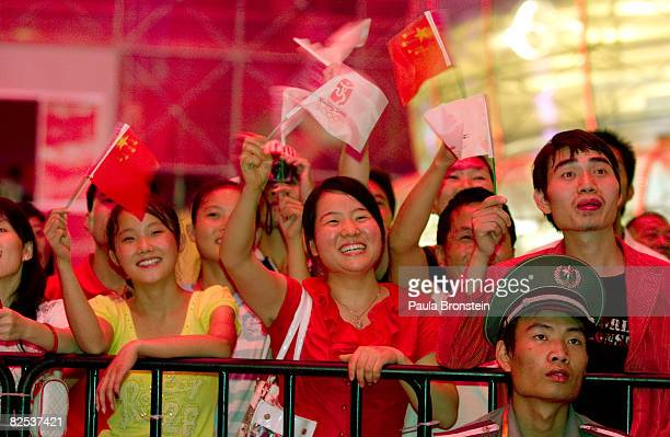 Chinese people watch the closing ceremony on a big screen at The Shuang Zone sponsored by Coca Cola August 24 2008 in Beijing The Olympics games has...