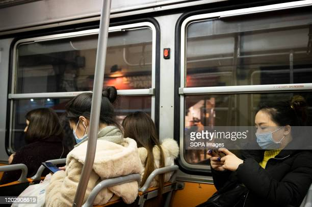 Chinese people wear face masks on a tram from the hospital. With an increasing toll of confirmed cases of people infected by Coronavirus and two...