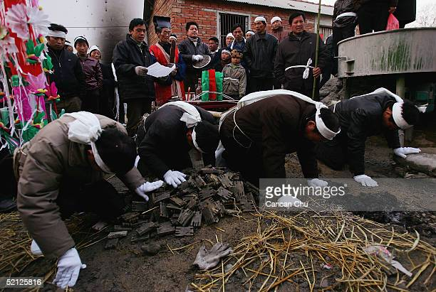 Chinese people wearing a white band around their heads attend the funeral of a relation on February 2 2005 in Jinzhai County Anhui Province China The...