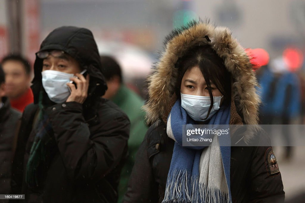 Chinese people wearing face masks prepare to travel at the Beijing Railway Station on January 31, 2013 in Beijing, China. The Spring Festival travel season runs from January 26 to March 6 and according to reports road passenger transport in China is estimated at 3.1 billion people during this time of year.