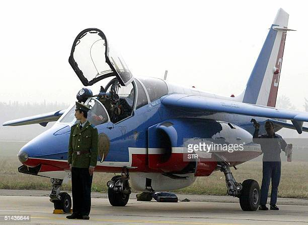 Chinese People's Liberation Army air force personnel guards the La Patrouille de France the French Air Force aerobatic team's Alpha jet prior to a...