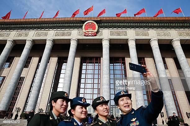 Chinese People's Liberation Army Delegates pose for a selfie outside the Great Hall of the People before the third plenary session of China's...
