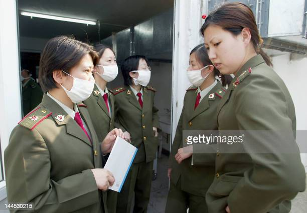 Chinese People's Liberation Army medical staff gather outside a nearly completed ward at the hospital erected in barely a week to house a rapidly...