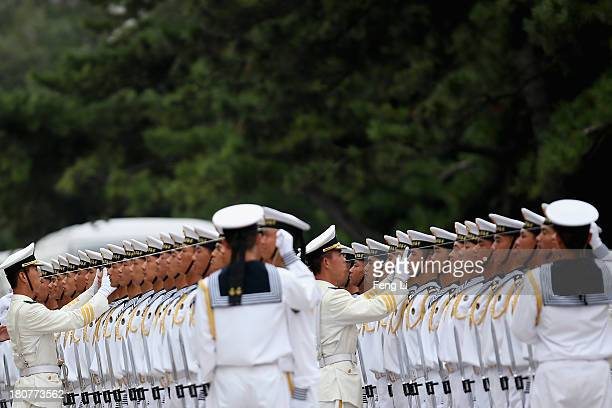 Chinese People's Liberation Army navy soldiers and officers use ropes to measure positions of honor guard members before a welcoming ceremony for...