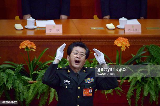 A Chinese People's Liberation Army officer conducts delegates singing the national anthem at the closing session of the Chinese People's Political...