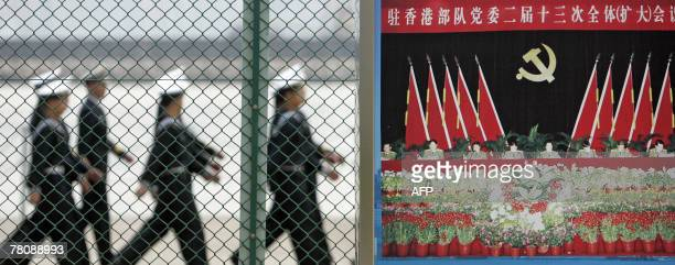 Chinese People's Liberation Army sailors pass a Communist propaganda poster at a PLA naval base in Hong Kong 25 November 2007 PLA troops usually...