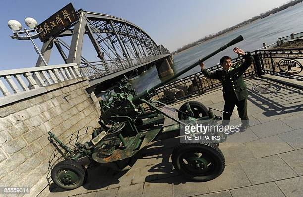 A Chinese People's Liberation Army soldier plays with an old antiaircraft gun on a visit to 'Broken Bridge' in Dandong on March 23 2009 which...