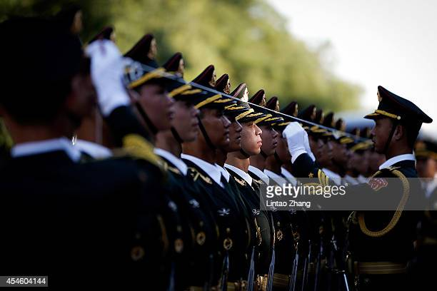 Chinese People's Liberation Army soldiers and officer use ropes to measure positions of honor guard members before a welcoming ceremony for...