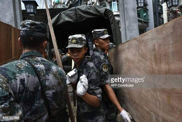 Chinese People's Liberation Army soldiers based at a barracks in Macau load debris onto their truck in Macau on August 25 two days after Typhoon Hato...