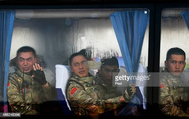 Chinese People's Liberation Army troops look out from a bus as they arrive at Tiananmen Gate to take part in a military parade to commemorate the...