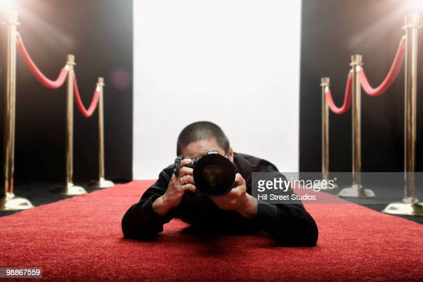 Chinese photographer laying on red carpet