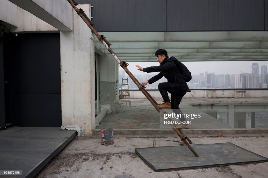 Chinese photographer Yan Lei climbs a ladder to reach a rooftop on a high building and take pictures of Chengdu on February 12, 2018. Yan Lei stands perched on the roof of a skyscraper, his feet just metres from the edge as his camera pans out on the spectacular urban landscape of Chengdu, southwestern China. /