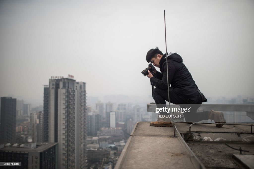 Chinese photographer Yan Lei takes pictures from a rooftop on a high building, in Chengdu on February 12, 2018. Yan Lei stands perched on the roof of a skyscraper, his feet just metres from the edge as his camera pans out on the spectacular urban landscape of Chengdu, southwestern China. /