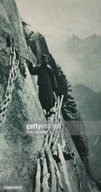 Chinese pilgrim walking along a cliff edge heading to the Taoist temple Mount Hua China photograph from The Illustrated London News vol 156 no 4222...
