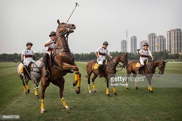 Chinese player Lin Yongyue second from left tries to control his horse as he and teammates leave the field after an exhibtion match against players...