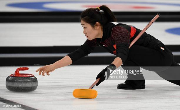 Chinese player takes part in a curling test event for the 2022 Beijing Winter Olympic Games at the National Aquatics Center, known as the Ice Cube,...