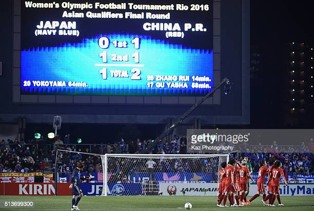 Chinese players celebrate while Aya Miyama of Japan walks off the pitch after the AFC Women's Olympic Final Qualification Round match between Japan...