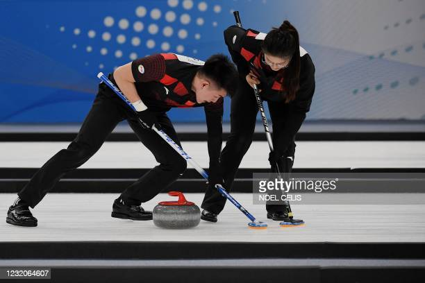 Chinese players take part in a curling test event for the 2022 Beijing Winter Olympic Games at the National Aquatics Center, known as the Ice Cube,...