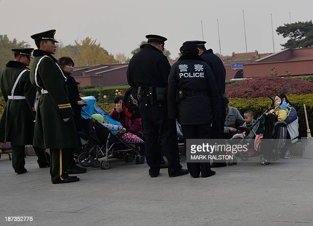 Chinese police and paramilitary police question a group of young mothers at Tiananmen Square as security is incresed on the eve of an important...
