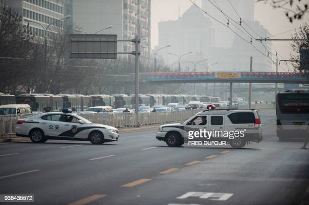 Chinese police cars block a road as a procession believed to be North Korean officials pass near Diaoyutai State Guesthouse in Beijing on March 27...