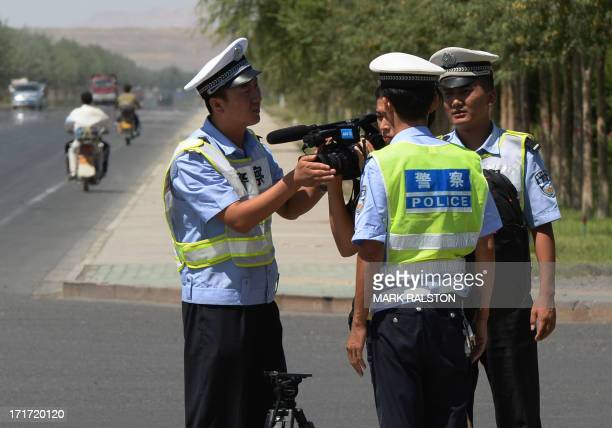 Chinese police detain a journalist at a checkpoint on the road to the riotaffected Uighur town of Lukqun Xinjiang province on June 28 2013 Fresh...