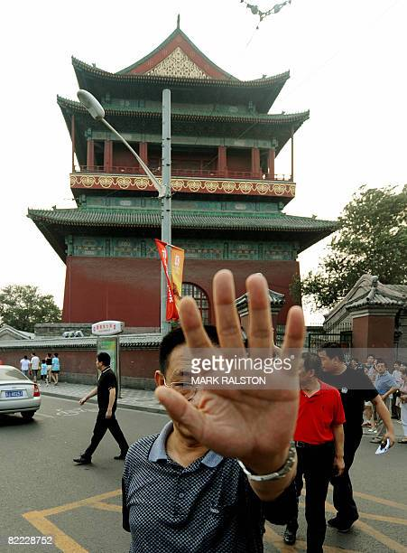 Chinese police detective blocks the camera as police leave the Drum Tower after investigating the scene where an American citizen was murdered in...