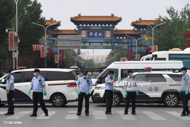 Chinese police guard the entrance to the closed Xinfadi market in Beijing on June 13, 2020. - Eleven residential estates in south Beijing have been...