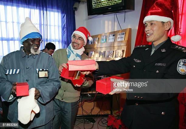 A Chinese police hands out gifts to foreign inmates at an evening held by the Shanghai Qingpu Prison to celebrate Christmas on December 24 2004 in...