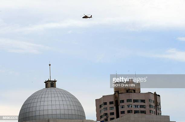 A Chinese police helicopter circles after several people were detained in a disturbance along a street in Urumqi China's farwest Xinjiang region on...