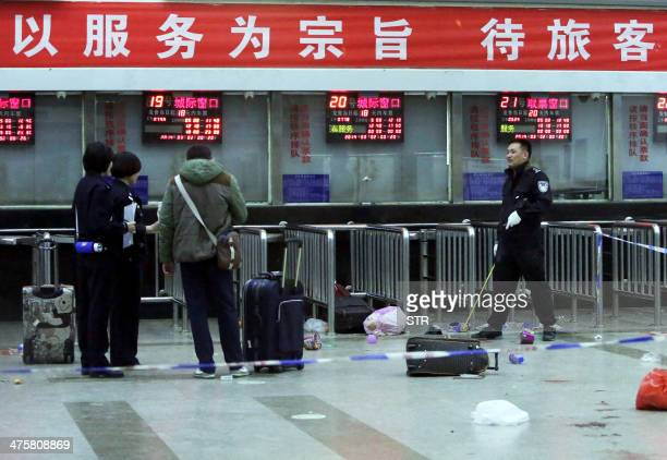 Chinese police investigators inspect the scene of an attack at the railway station in Kunming, southwest China's Yunnan province, on March 2, 2014. A...