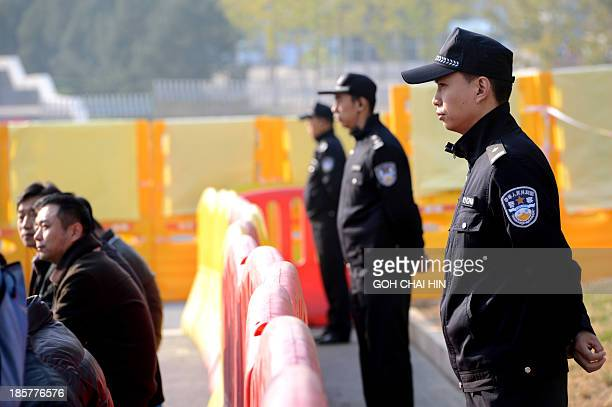 Chinese police keep watch on members of the media outside the gate of the Shandong high court building in Jinan east China Shandong province on...
