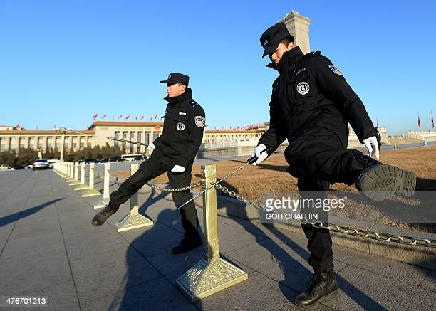 Chinese police make a security sweep of Tiananmen Square prior to the opening session of the 12th National People's Congress at the Great Hall of the...