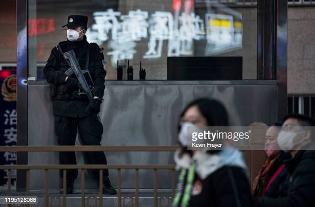 Chinese police officer on regular security duty wears a mask as he guards outside Beijing Railway station as masked travellers make their way to...