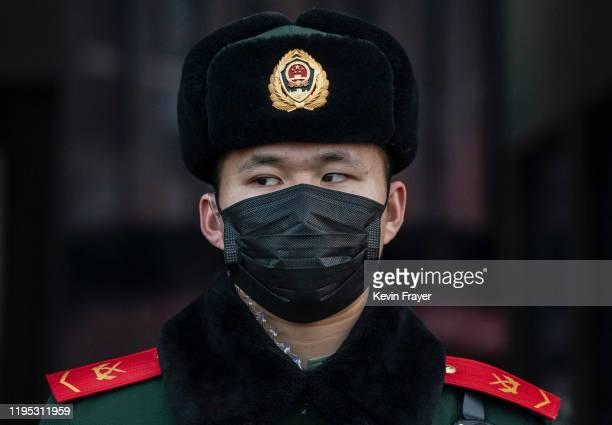 Chinese police officer wears a protective mask as he stands guard at Beijing Station before the annual Spring Festival on January 22 2020 in Beijing...