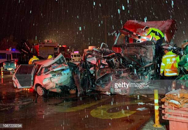 TOPSHOT Chinese police officers and rescuers work at the site of where a truck ploughed into cars at a toll booth in Lanzhou in China's northwestern...