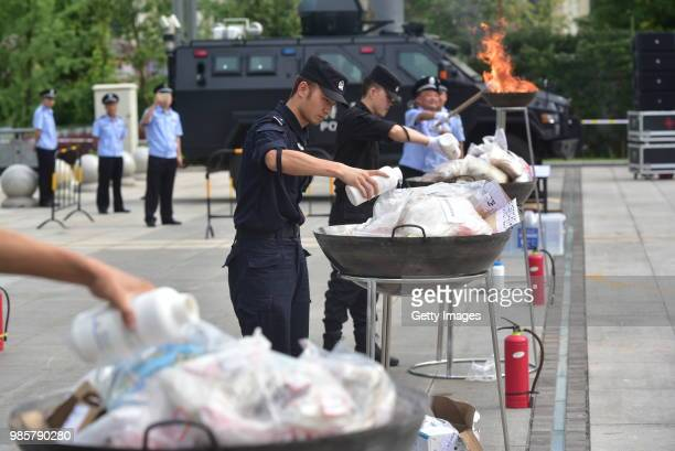 Chinese police officers destroy about 57 kilograms of drugs to mark the 31st International Day Against Drug Abuse and Illicit Trafficking on June 26,...