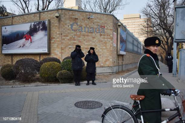 Chinese police officers stand guard outside the Canadian embassy in Beijing as a paramilitary police officer walks his bicycle on December 10 2018...