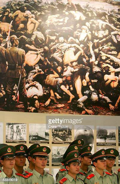 Chinese police officers view drawings and pictures from the 1937 Nanjing Massacre during an exhibition of historical facts on the massacre at the...