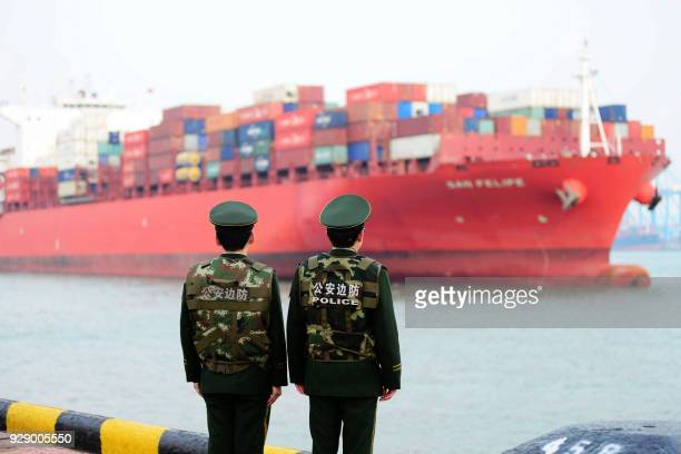 Chinese police officers watch a cargo ship at a port in Qingdao in China's eastern Shandong province on March 8, 2018. China's trade surplus with the...