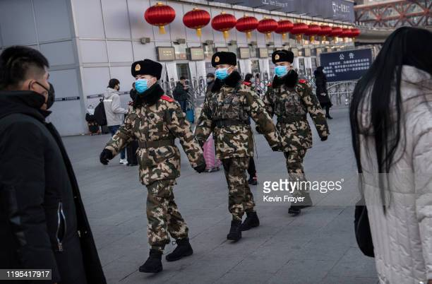 Chinese police officers wear protective masks as they patrol before the annual Spring Festival at a Beijing railway station on January 23 2020 in...