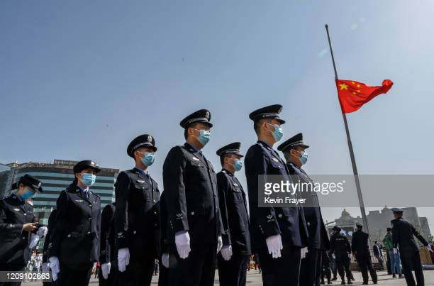 Chinese police officers wear protective masks as they stand in formation next to a national flag at half staff just before three minutes of silence...