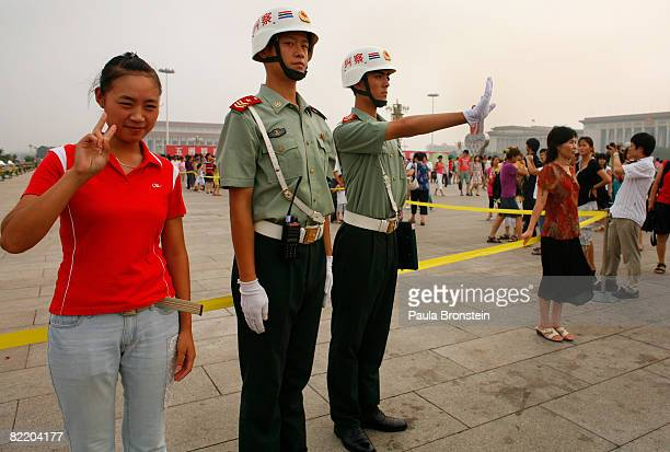 Chinese police signal for people to stop photographing them as a Chinese tourist poses for the camera in Tianamen Square one day before the opening...