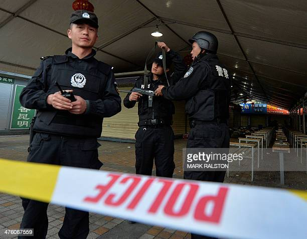 Chinese police stand guard at the scene of an attack at the main train station in Kunming, Yunnan Province on March 2, 2014. Knife-wielding...