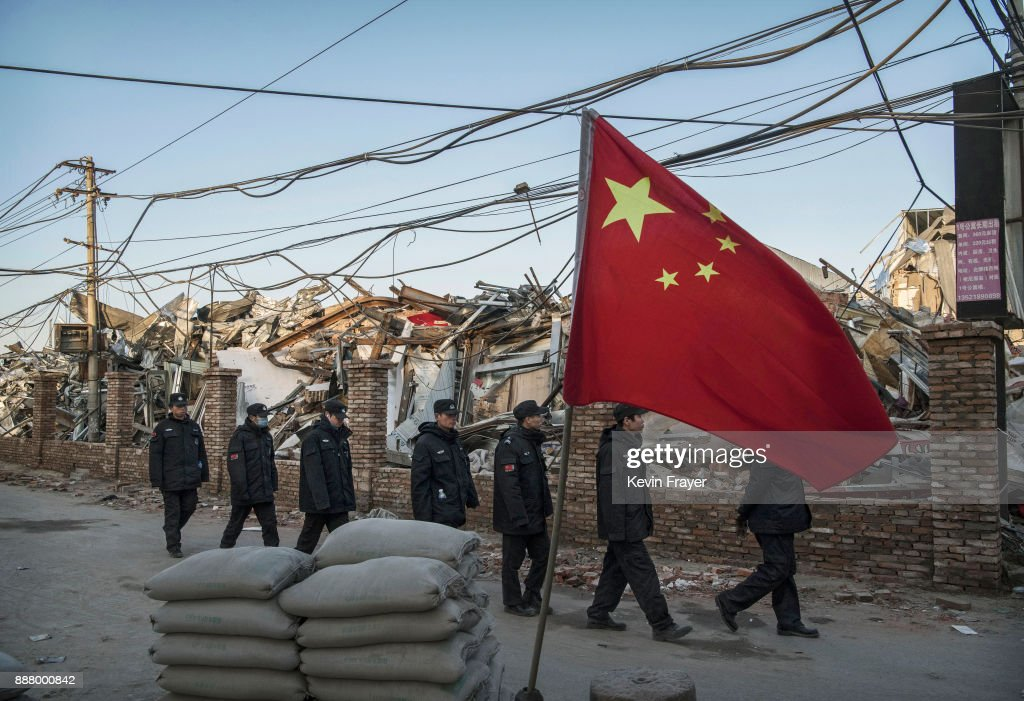 Chinese police walk in a line passed buildings demolished by authorities in an area that used to have migrant housing and factories on December 6, 2017 in the Daxing District of Beijing, China.Thousands of migrant workers have been forcibly evicted in recent weeks in a sweeping government safety campaign following a deadly fire at a housing settlement. Many migrants, who came to Beijing from poor rural areas to find employment, say they were given little notice to leave and cannot afford to move somewhere else. The government's plan to demolish the buildings was actually announced in a 2015 strategy to reduce and cap the capital's population, but the mass evictions were accelerated after the fire and have stirred public backlash. The migrant population typically work in jobs such as construction, sanitation, and deliveries that have effectively built Beijing and keep it running. Some companies announced assistance and temporary housing for employees who have been affected, but many migrants say they have little choice but to move back to their hometowns.
