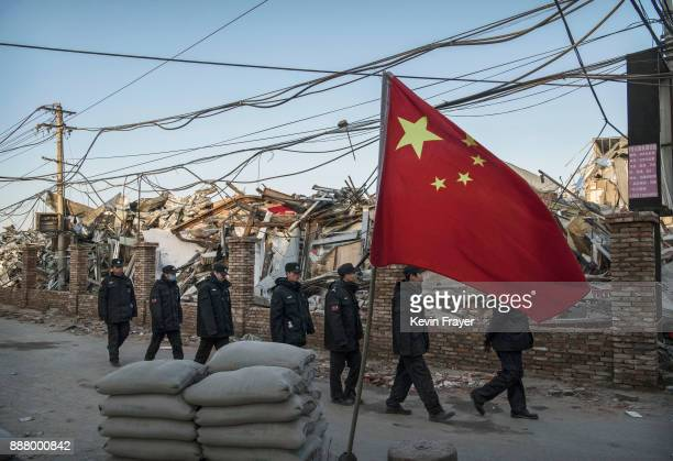 Chinese police walk in a line passed buildings demolished by authorities in an area that used to have migrant housing and factories on December 6...