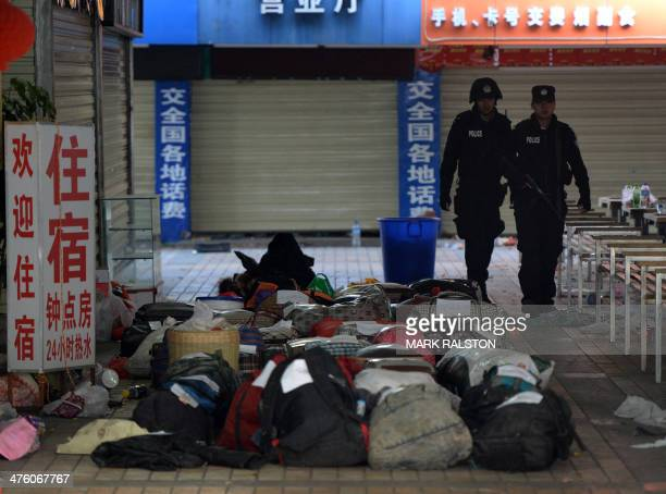 Chinese police walk past abandoned luggage at the scene of an attack at the main train station in Kunming, Yunnan province on March 2, 2014....
