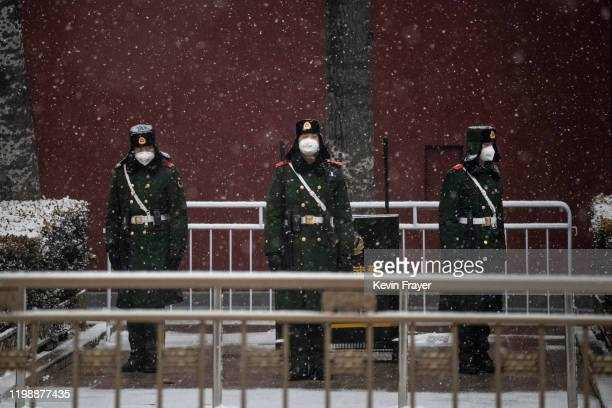 Chinese police wear protective masks as they stand on the main road leading to Tiananmen Square on February 5, 2020 in Beijing, China. China's stock...